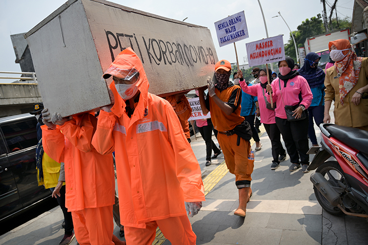 Local officials carry a mock coffin to promote awareness over the COVID-19 coronavirus in Jakarta on September 15, 2020.